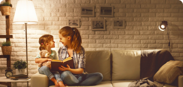 Mother and daughter reading on the couch in a modern home